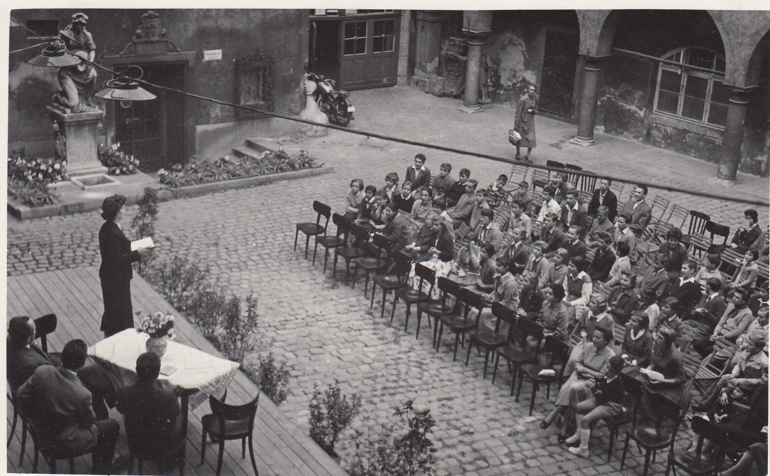 Fotka zo šesťdesiatych rokov zobrazuje publikum školopovinných detí. Sedia na stoličkách rozložených na nádvorí Starej radnice.