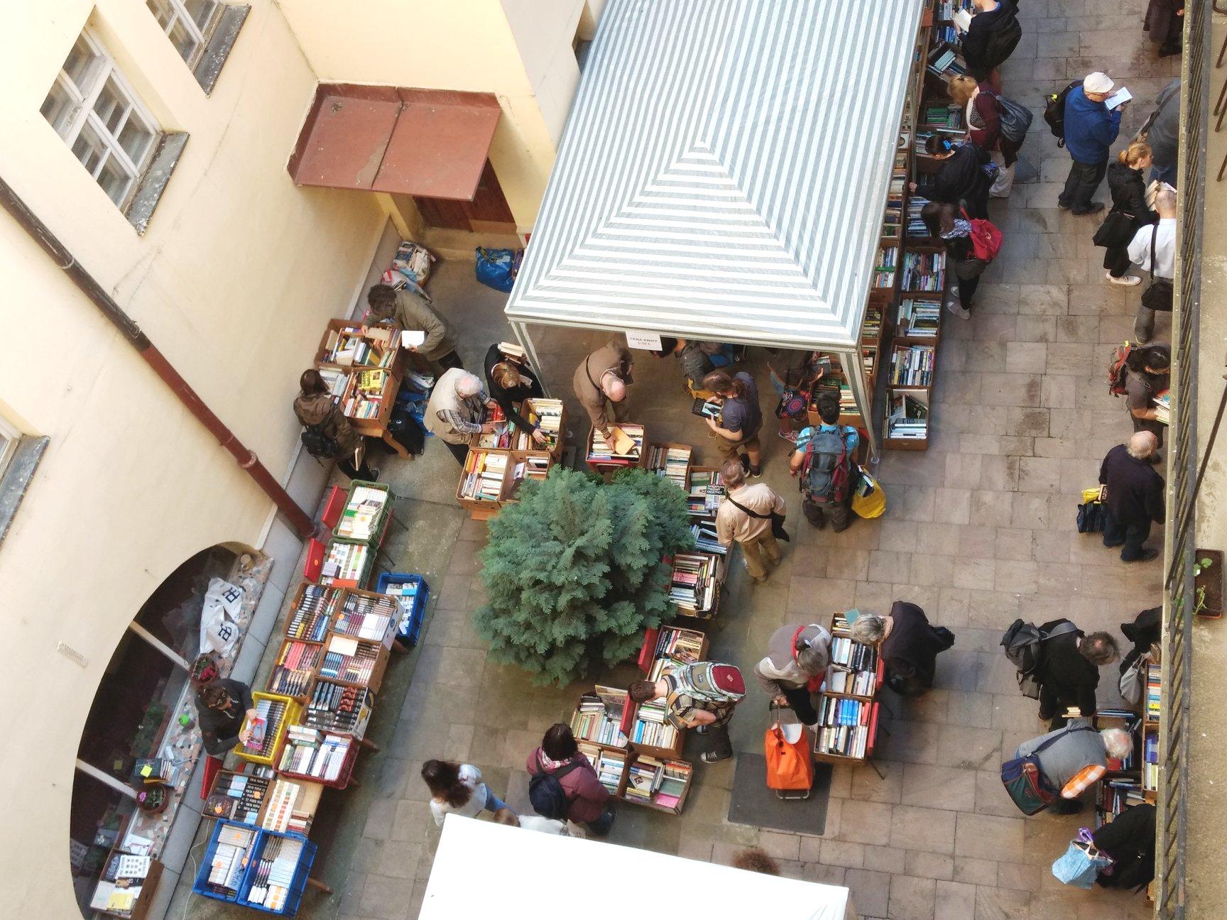 Fotografia zachytáva pohľad na burzu zvtáčej perspektívy. Vpravej časti je pásikavá strieška stánku, na celej ploche sú rozložené krabice sknihami, ktoré si prezerajú návštevníci.