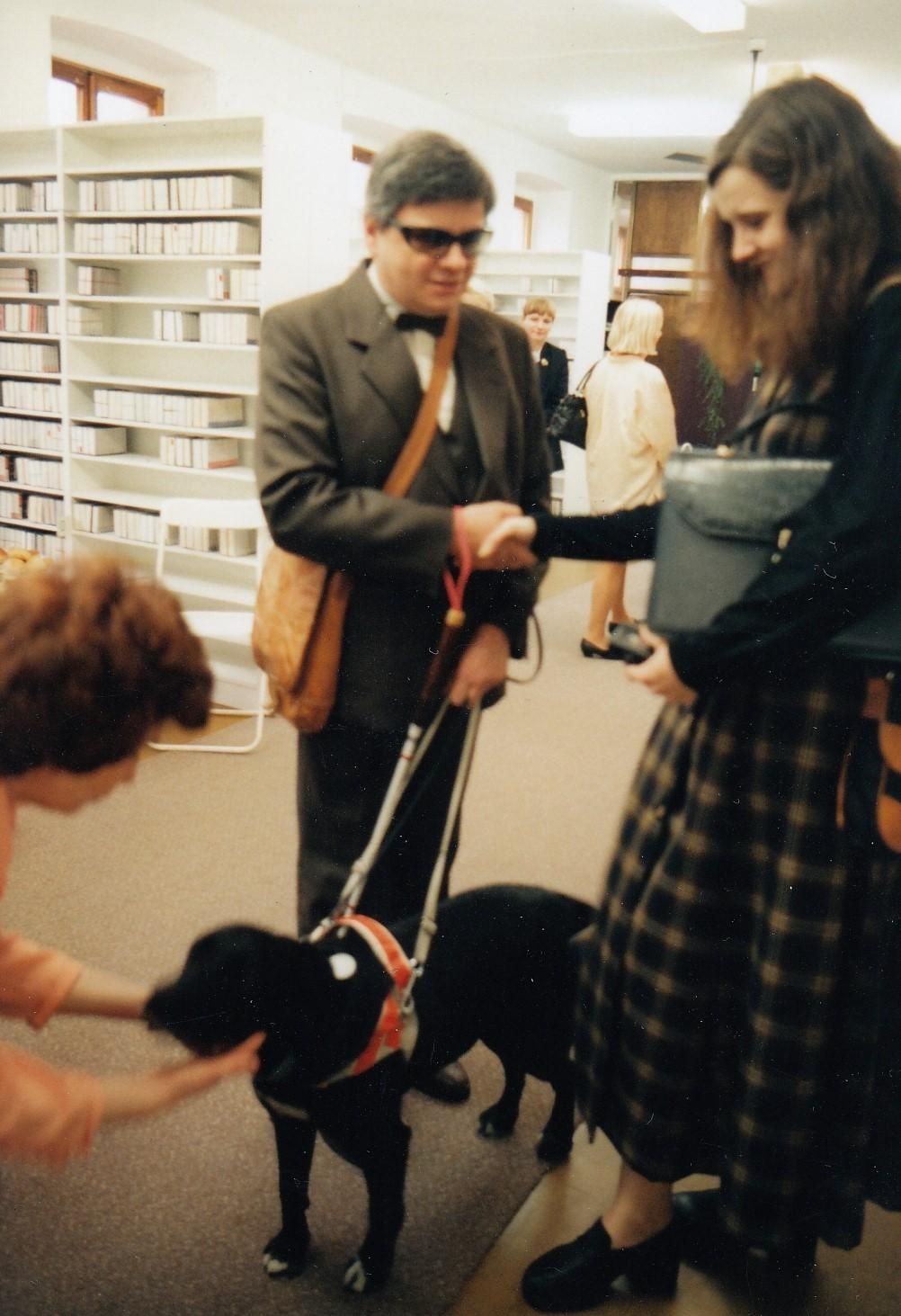 Na fotke zdeväťdesiatych rokov je muž stmavými okuliarmi, bielou paličkou avôdzkou svodiacim psom. Podáva si ruku sdlhovlasou ženou. Vpozadí sa nachádzajú ďalší ľudia aregály so zvukovými knihami.