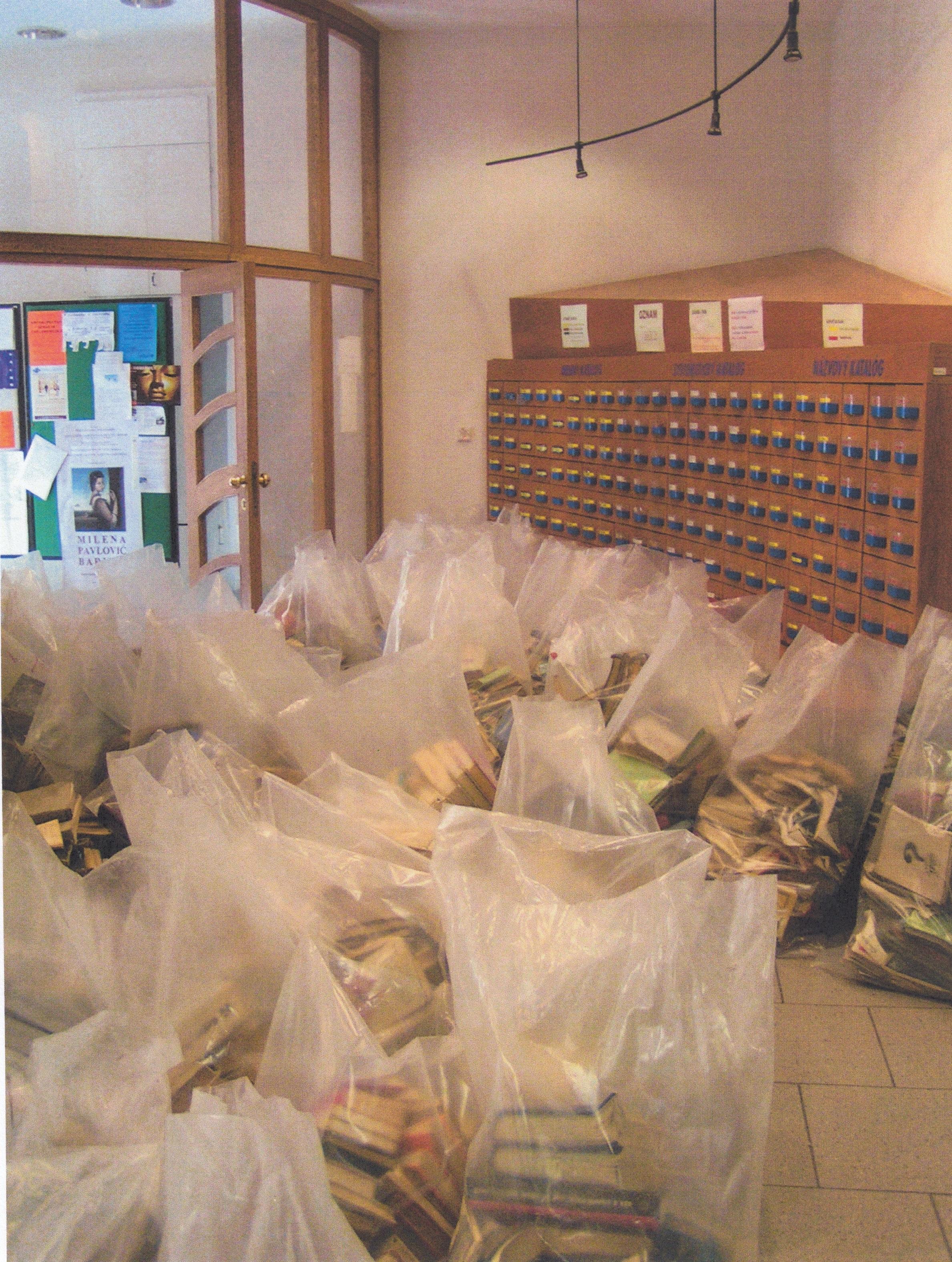 Na fotke je množstvo odpadových vriec spoškodenými knihami. Vpozadí je regál na kartotečné lístky, nástenka avchod do knižnice.