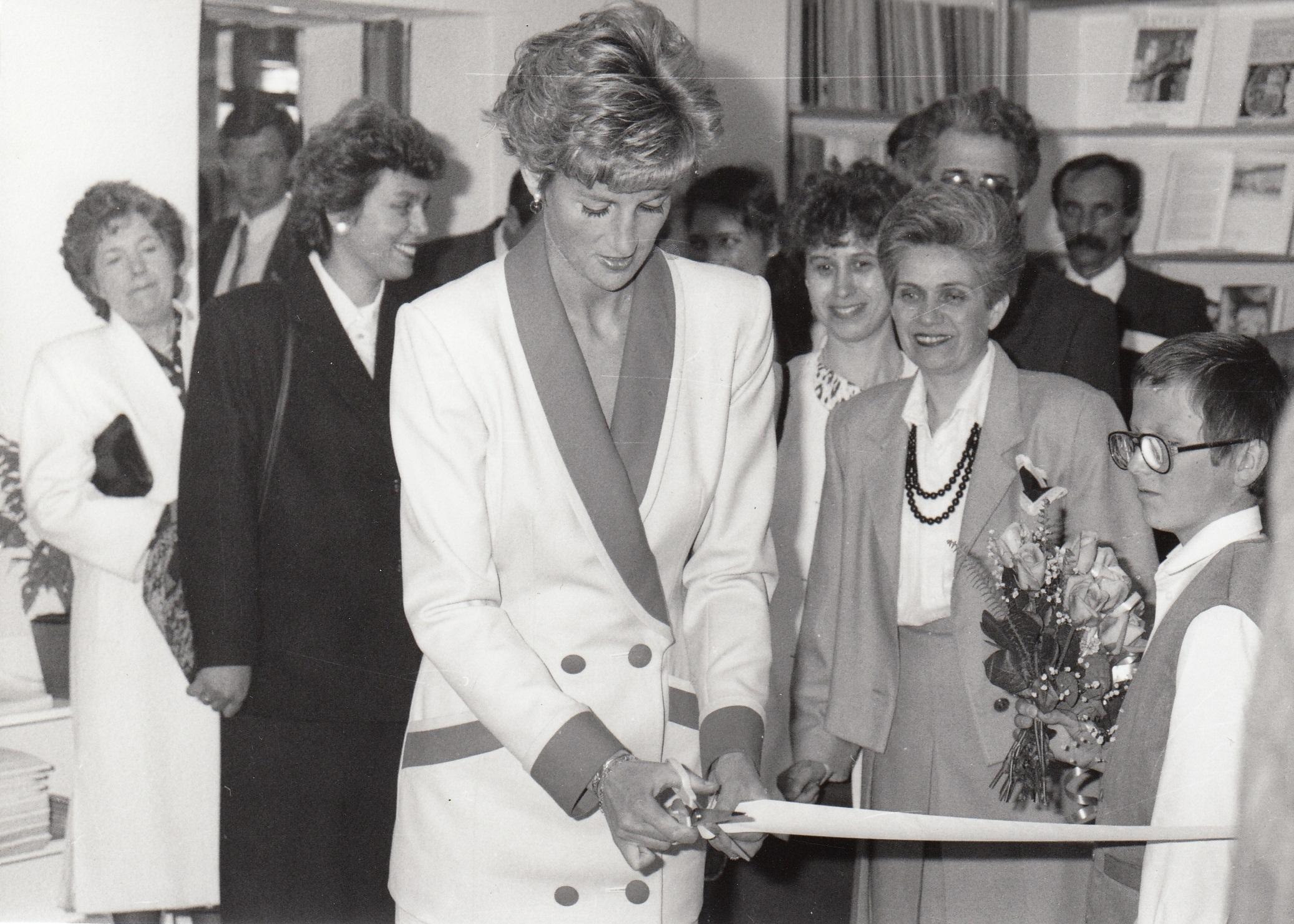 Princezná Diana vo svetlom kostýme prestriháva pásku.